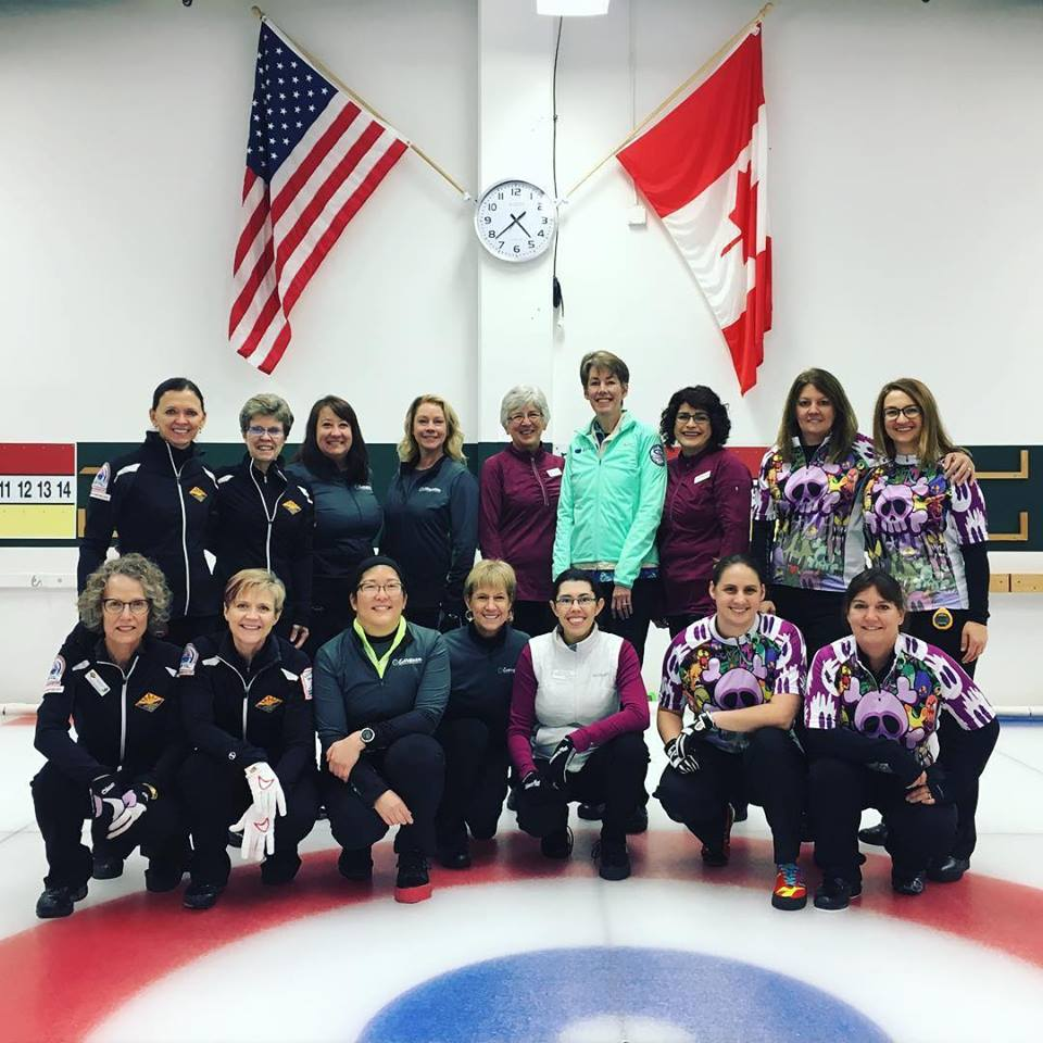16 women making four curling teams stand in a curling rink