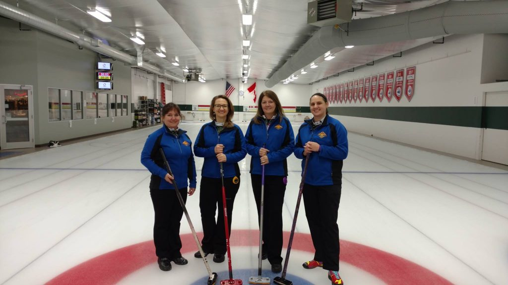 Four women stand in a curling rink.
